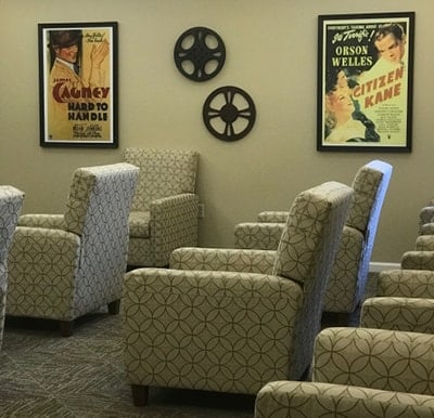 A movie theater room at a senior living community with reclining chairs.