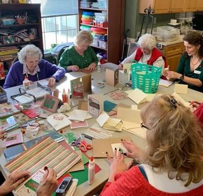 Senior women gathered around a table making christmas crafts.