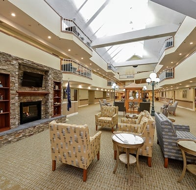 Atrium featuring a fireplace with built in shelving, multiple seating areas and an American flag.