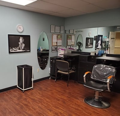 Beauty salon with multiple stations and images of movie stars on the walls.