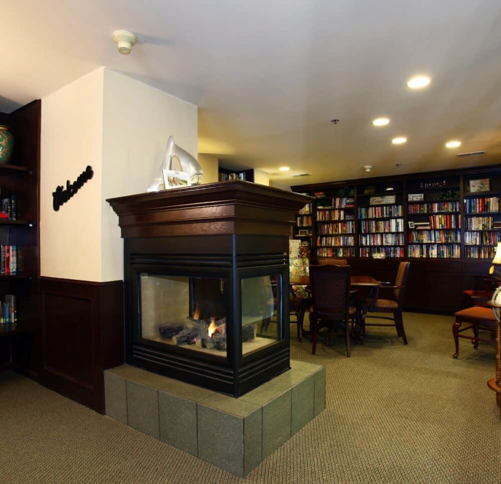 Library area with a fireplace at a senior living facility in Omaha, Nebraska.
