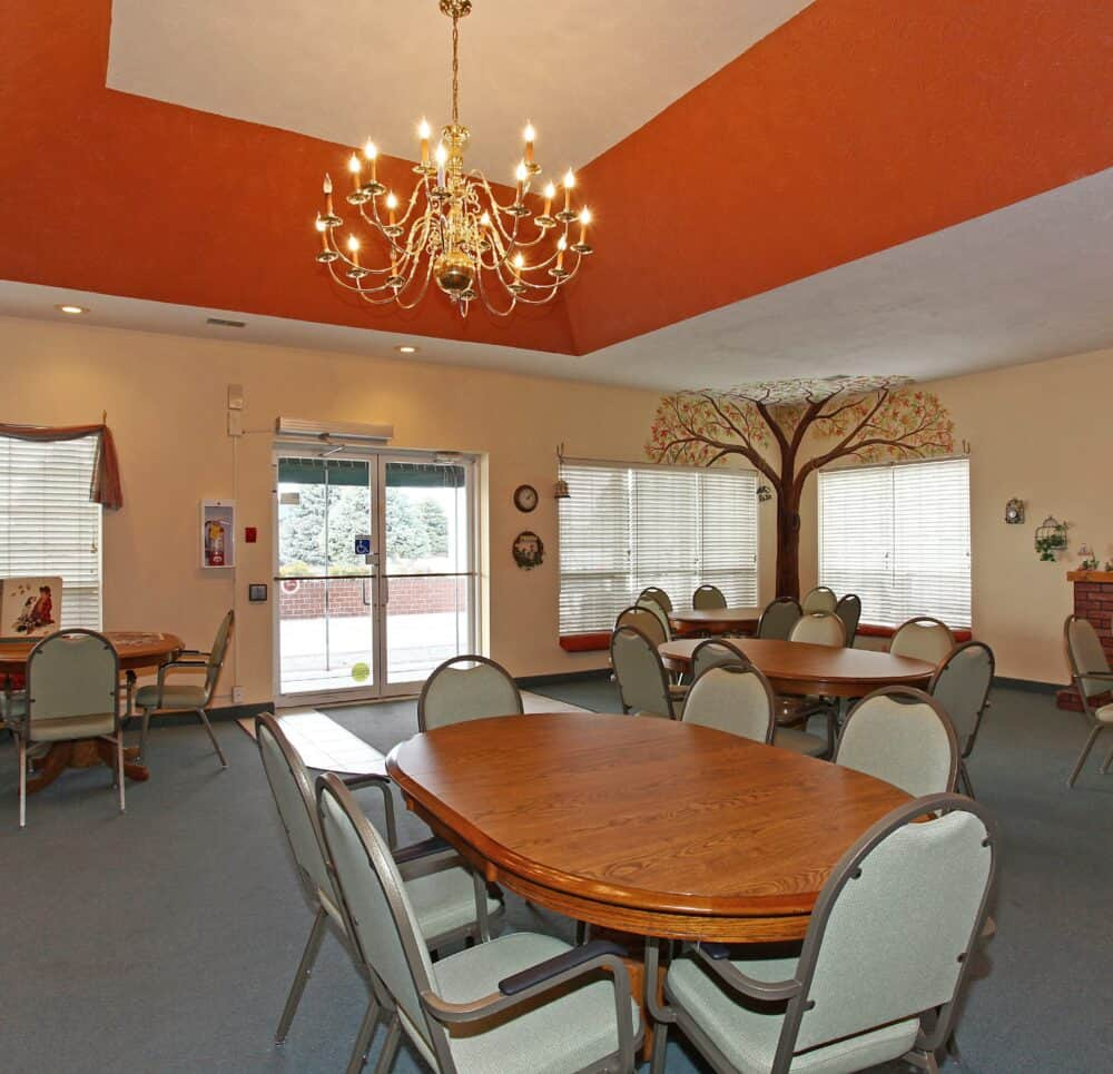 Activity room with tables and chairs at senior living facility in Plattsmouth, Nebraska.