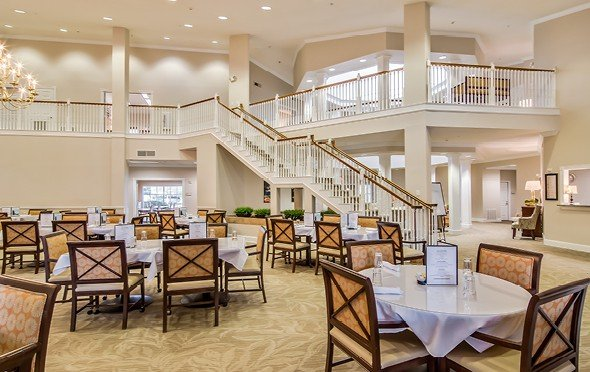 Large and elegant dining room with high ceilings and a grand staircase leading down from the upper level in San Antonio, Texas.