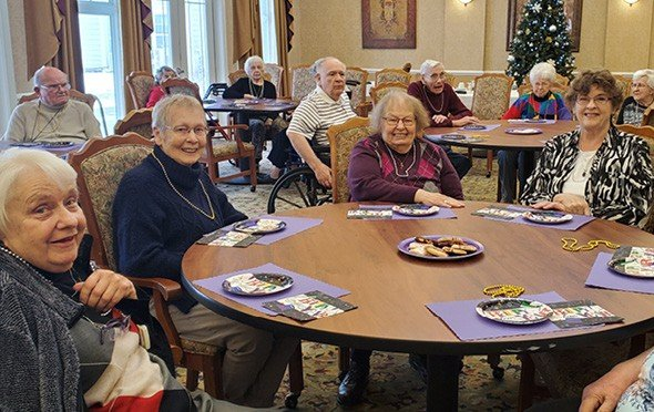 Smiling residents sitting around tables in the dining area in Perrysburg, Ohio.