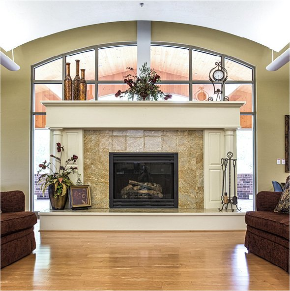 Great room of senior living community in Green Bay Wisconsin with a large fireplace with windows behind it and two beige sofas in front.