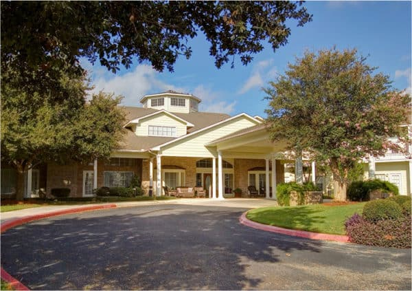 The exterior of a senior living community in San Antonio, Texas, with comfortable seating on a covered patio, large trees and beautiful landscaping.