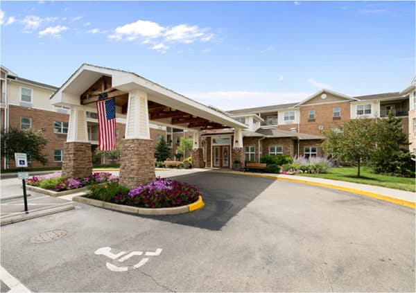 Front entrance of a senior living facility in Dayton, Ohio with lush landscaping and covered driveway.