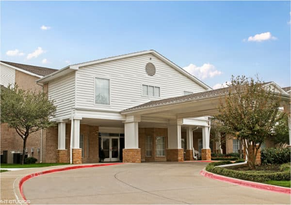 Front entrance of a senior living facility in North Richland Hills, Texas with covered circular driveway.
