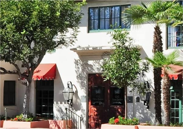 Front entrance of a senior living facility in Santa Barbara, California with a palm tree at the entrance.