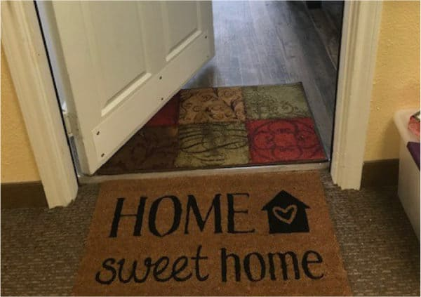 """An open door leading into an apartment with a floor mat that says """"Home, sweet home"""" in Fort Worth, Texas."""