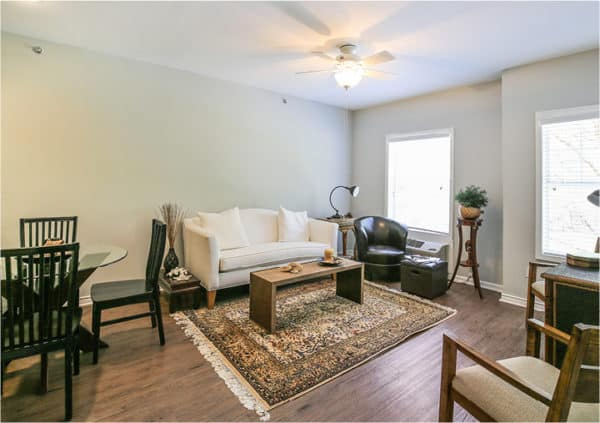 Interior of a resident apartment with a dining area and a large lounge area with sofa, coffee table and accent chairs in Ridgeland, Mississippi.