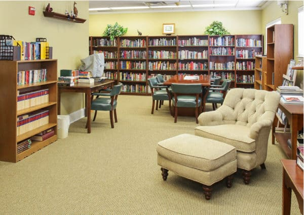 A large library with surrounding walls filled with bookshelves and a comfortable lounge chair among tables in Mesquite, Texas..