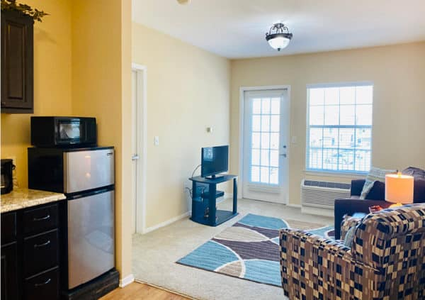 A bright and spacious living room and kitchenette in a model apartment home in North Richland Hills, Texas.