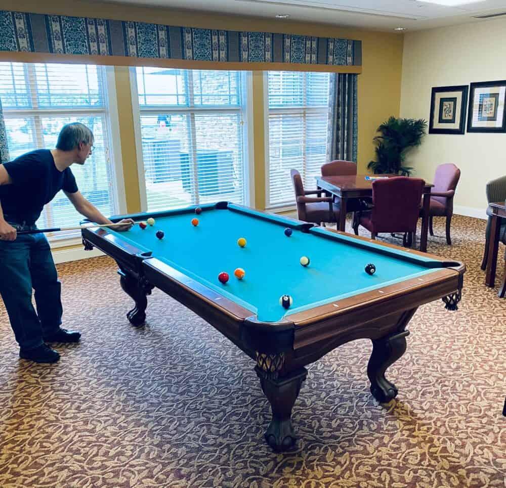 Senior man plays billiards at a senior living community in Dayton, Ohio.