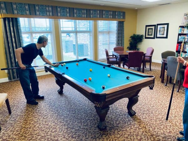 senior man plays billiards at the wellington at dayton, a senior living community in dayton, ohio
