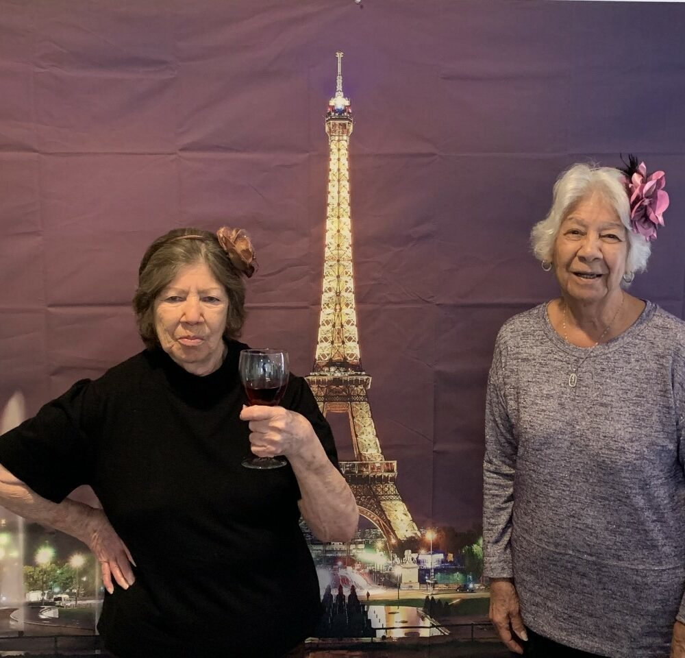 Senior ladies at a party with Paris decorations at a senior living community in Irving, Texas.
