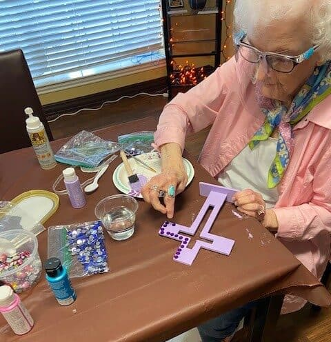 Senior woman doing a craft project at a senior living facility in Fort Worth, Texas.
