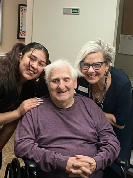 Two employees and a senior man smile at a senior living community in Cottonwood, Arizona.