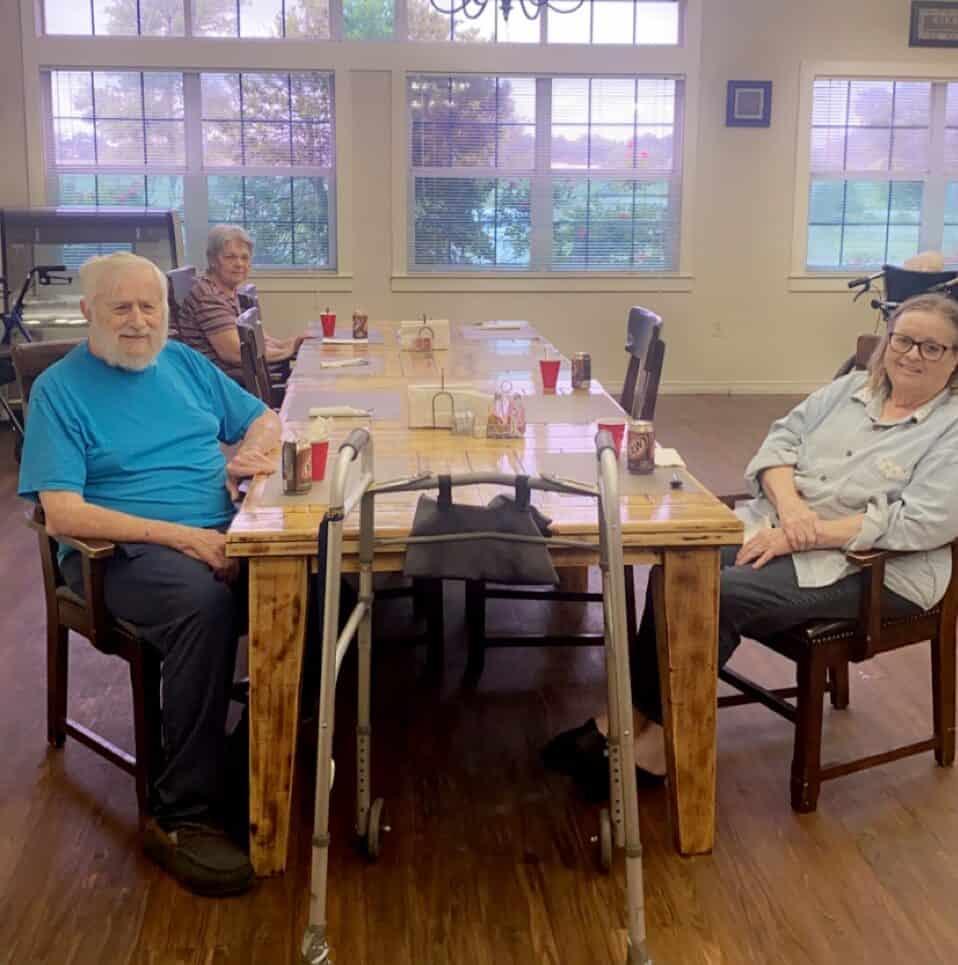 Two seniors smiling at dinner at Good Tree senior living in Stephenville, Texas.