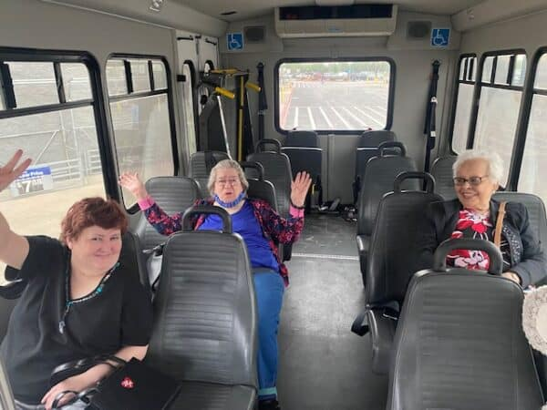 Three seniors smiling in a bus at Good Tree senior living in Stephenville, Texas