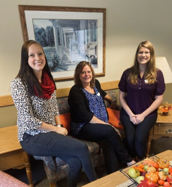 Three employees smile together while working at a senior living community in West Bend, Wisconsin.