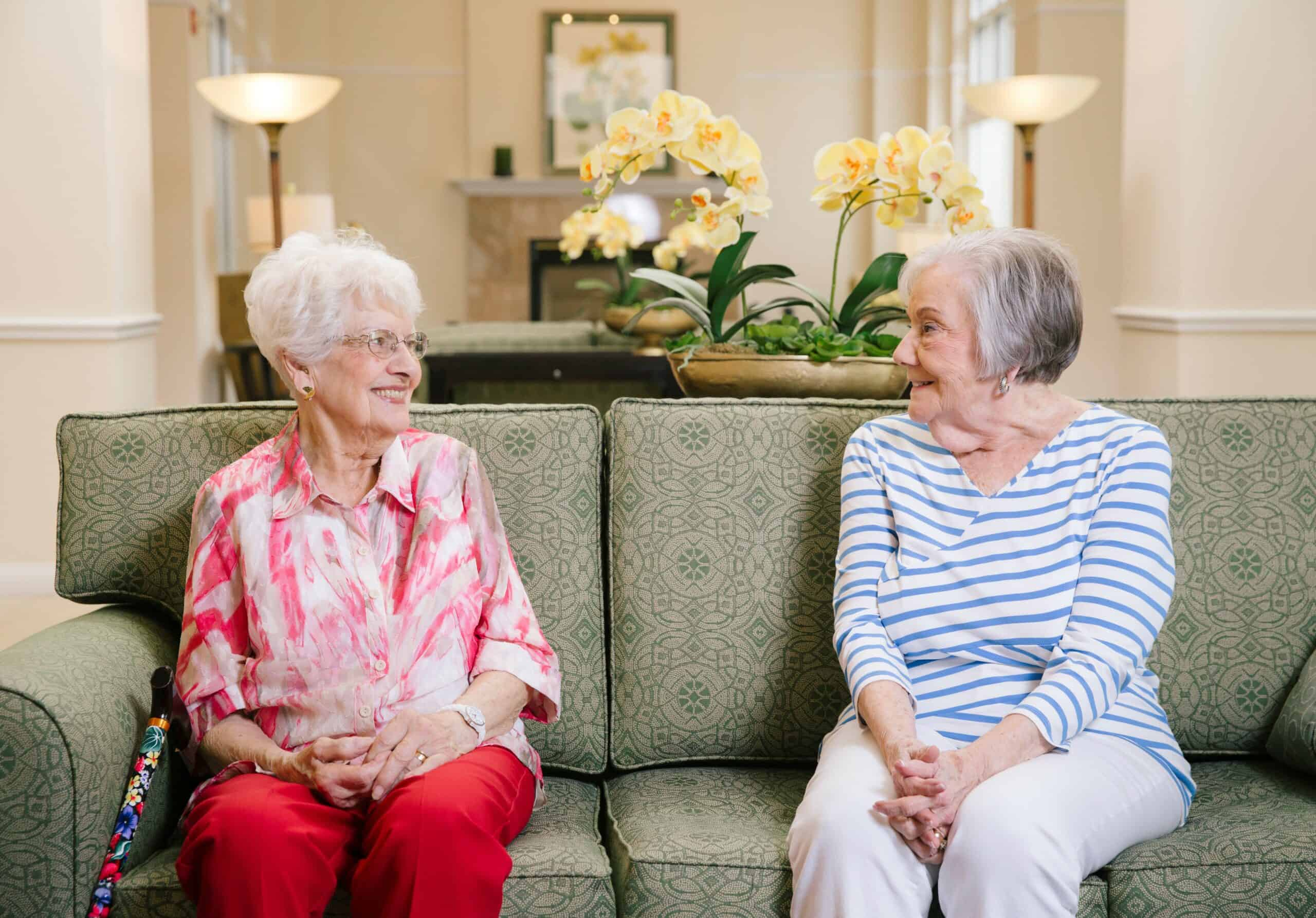 two senior women smile at each other at the Waterford at ironbridge senior living community in Springfield, Missouri
