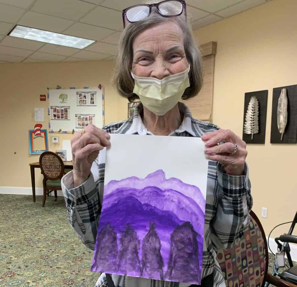 Senior woman poses with her watercolor painting at a senior living community in Plano, Texas.