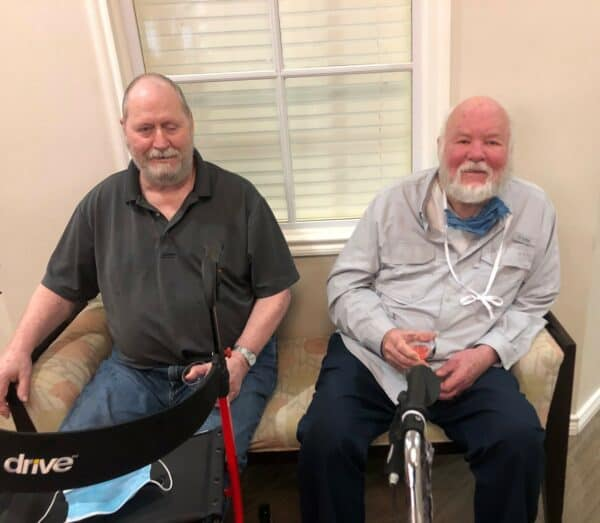 Two senior men smile at the camera at a senior living community in Ridgeland, Mississippi.