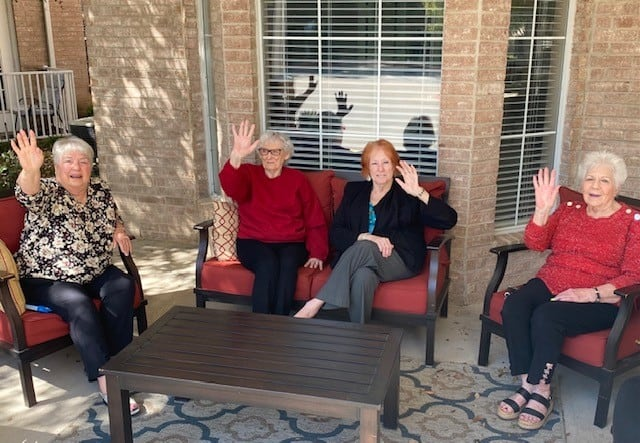 Senior women smile and wave at the camera at senior living community in North Richland Hills, Texas.