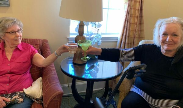 Two senior women smile with their drinks at a senior living community in Plano, Texas.
