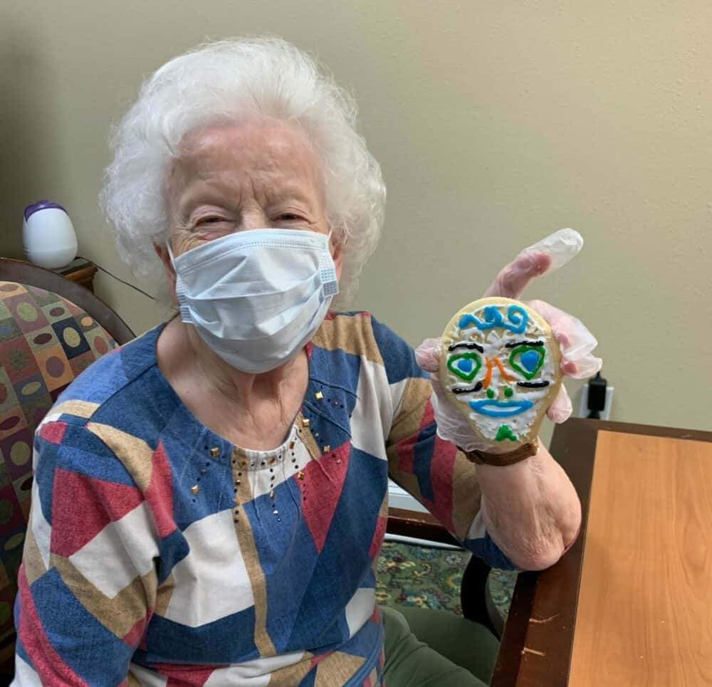 Senior woman poses with her decorated cookie at a senior living community in Plano, Texas.