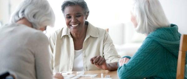 Senior women playing a game of dominos.