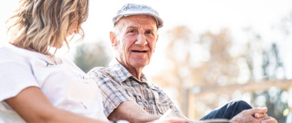 A man sitting on a bench talking about senior living with his daughter
