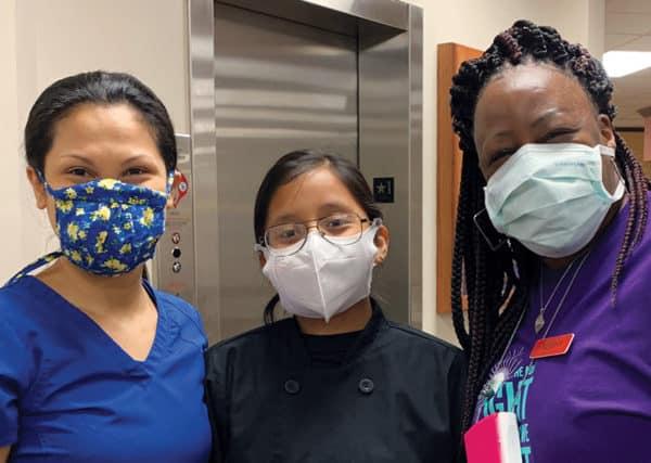 Three masked employees with smiling eyes.