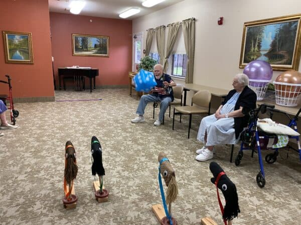 Senior man and woman playing a game of horse racing at a senior living facility in Granbury, Texas.