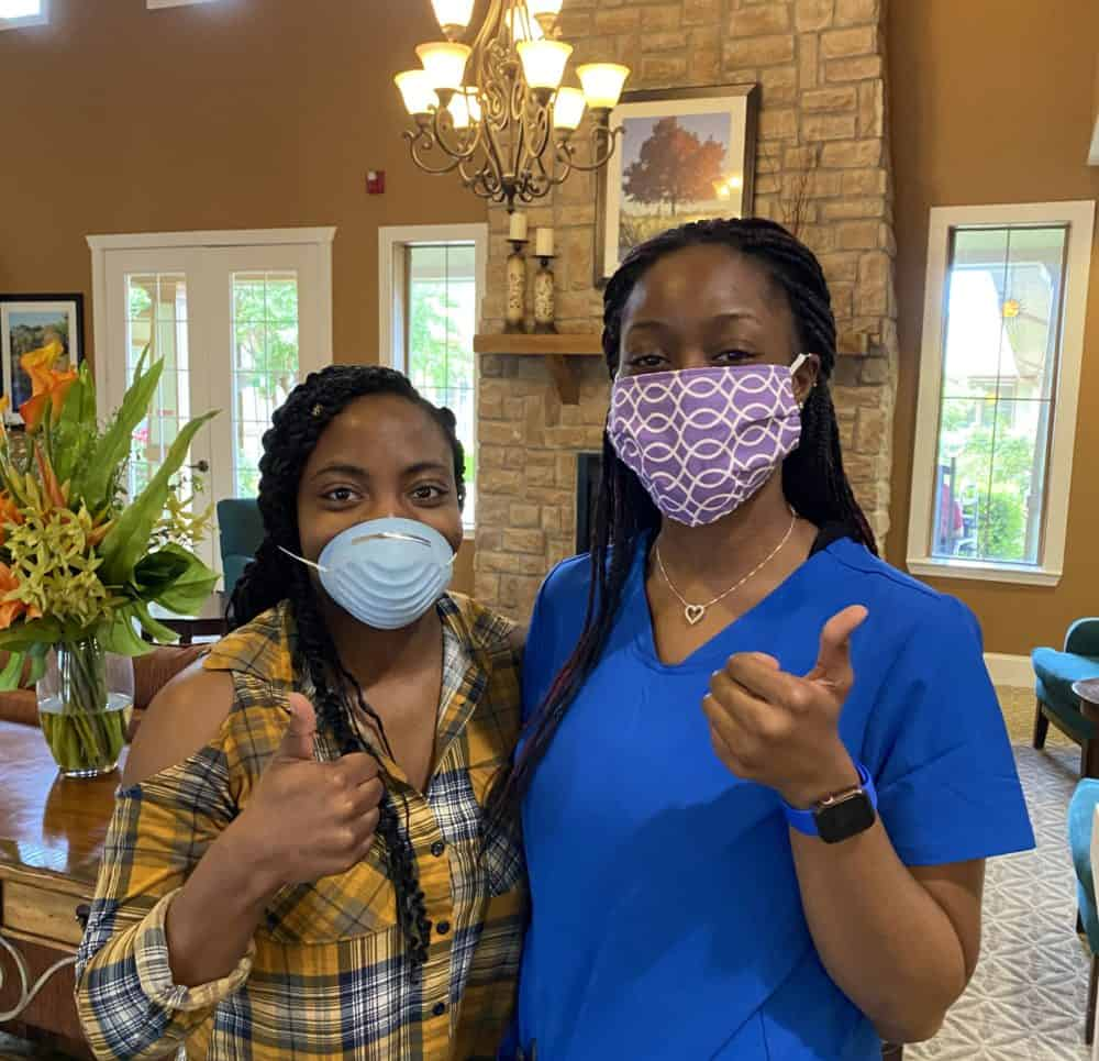 Two-women-caregivers-give-thumbs-up-in-senior-living-facility.