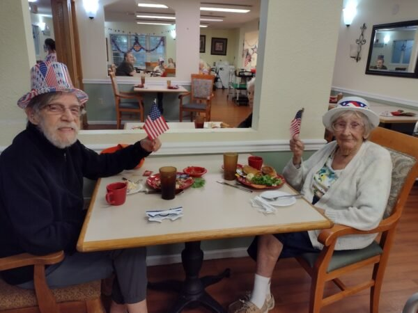 Senior woman and senior man eat together on the Fourth of July at a senior living community in Jeffersonville, Indiana.