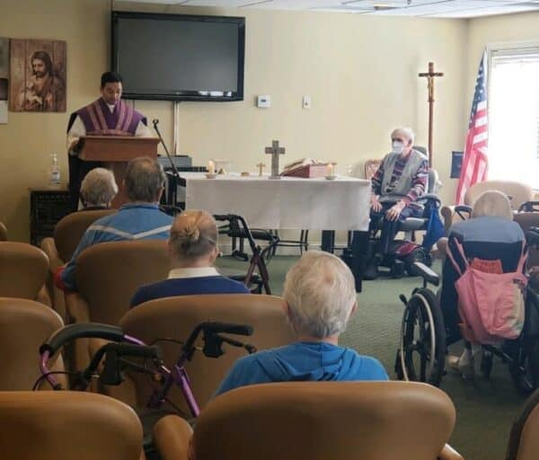 A priest giving a service to a group of seniors at a senior living community in Cincinnati, Ohio.