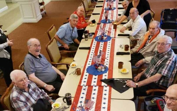 Group of senior men celebrate the Fourth of July during a group dinner at senior living community in Cincinnati, Ohio.