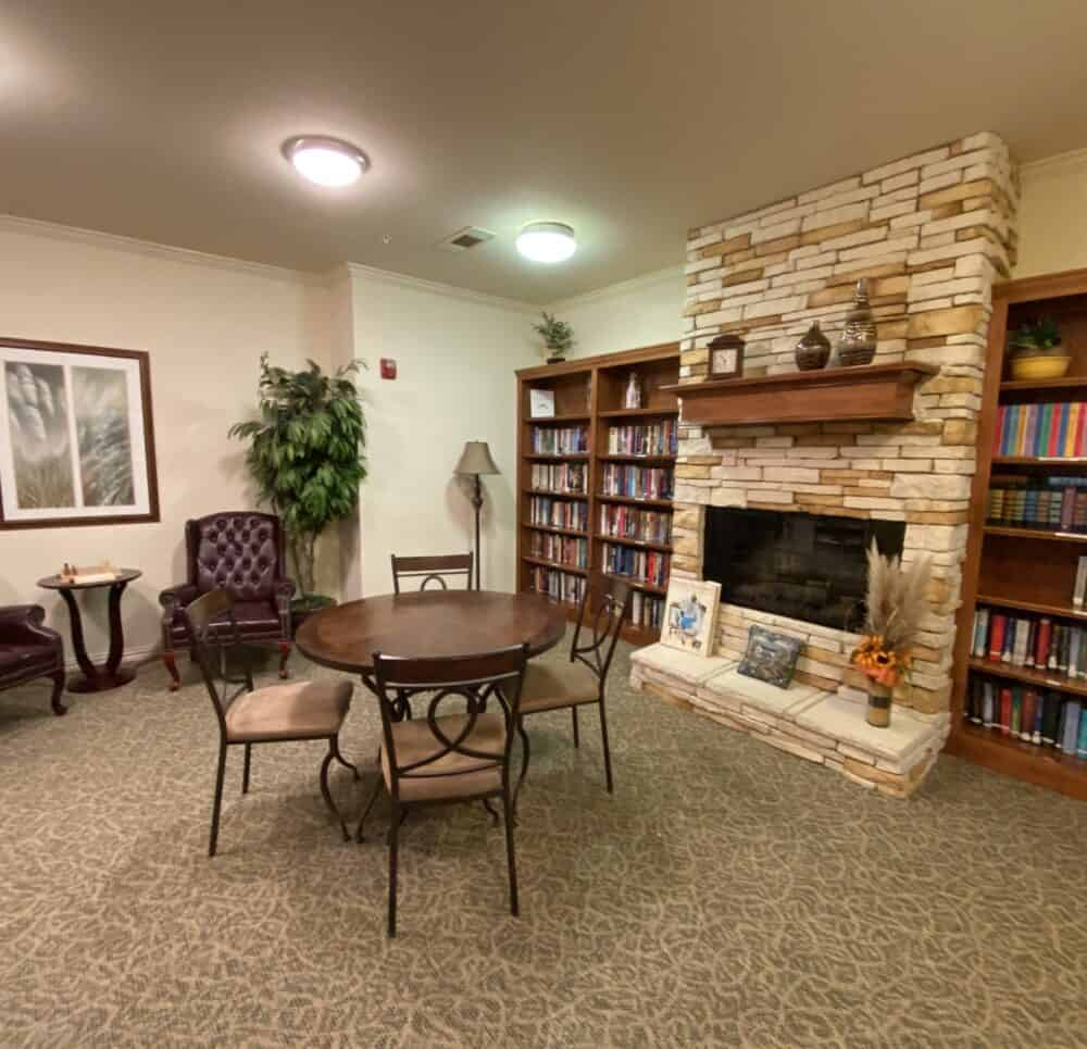 Library with seating and fireplace at a senior living community in Granbury, Texas.