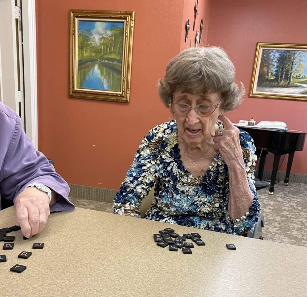 Senior woman plays Scrabble at the Courtyards at Lake Granbury, a senior living community in Granbury, Texas.