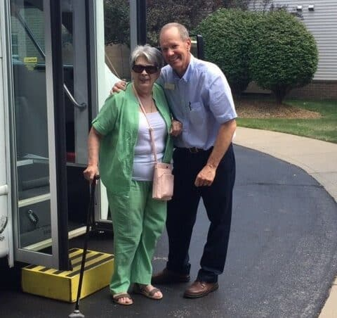senior woman smiles with a bus driver at the Waterford at ironbridge in Springfield, Missouri