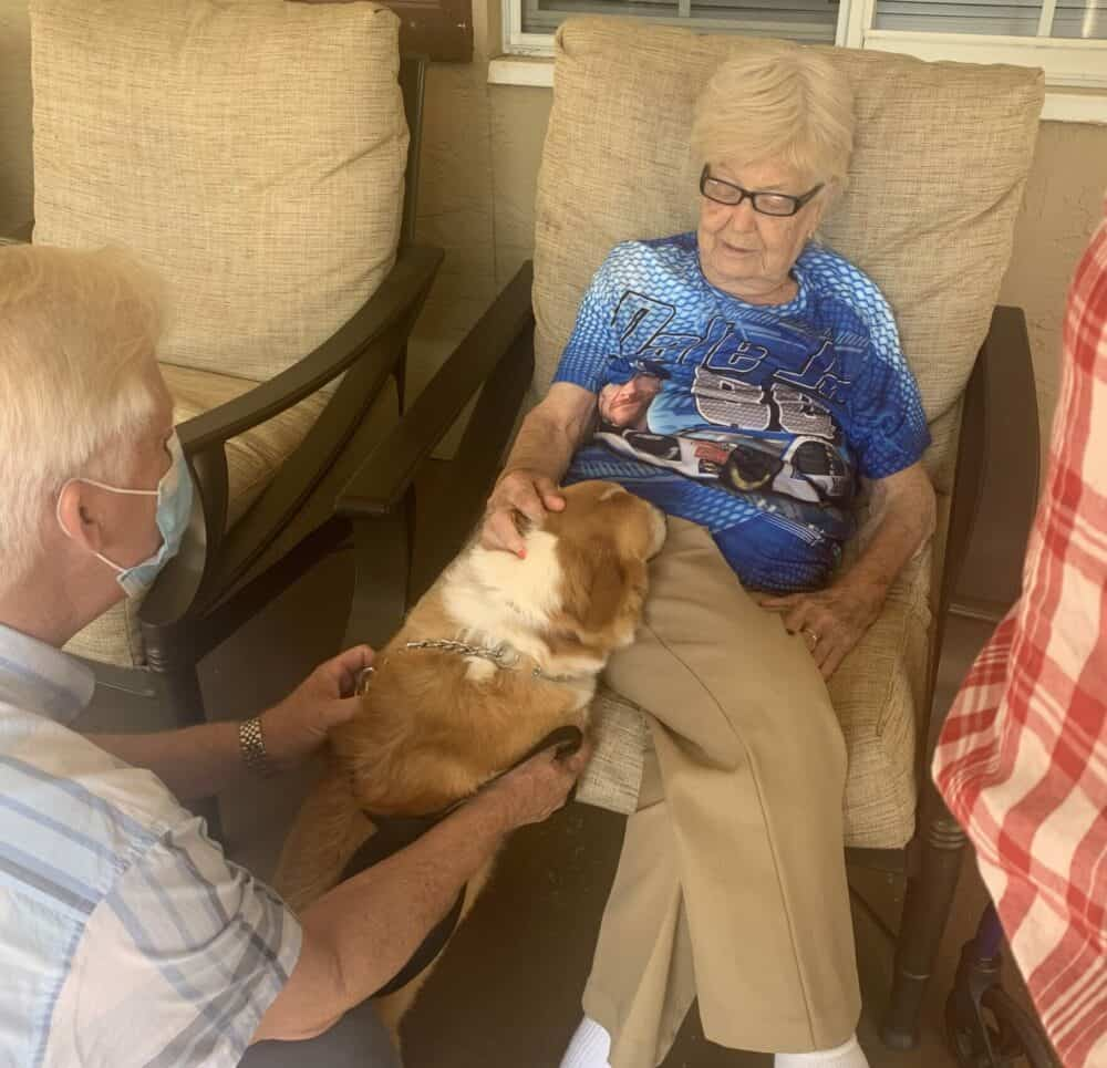Senior woman pets a therapy dog at a memory care community in Pensacola, Florida.