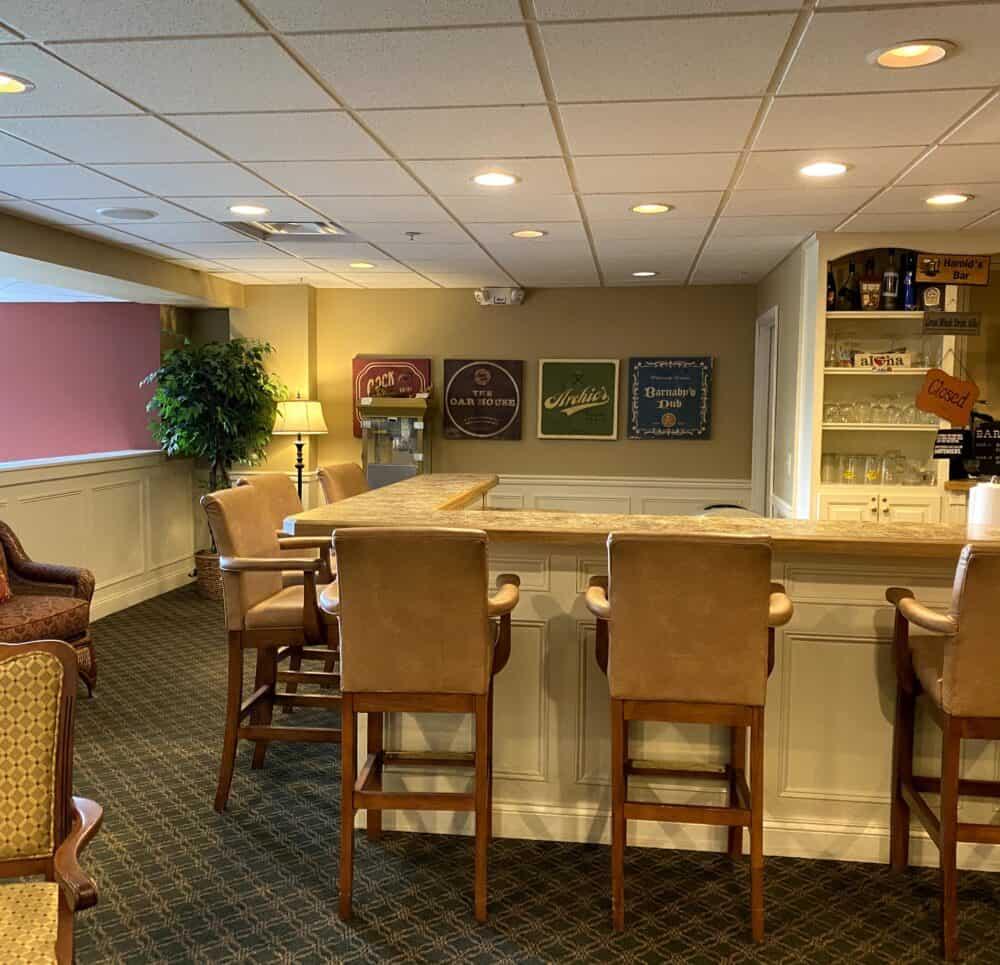 Pub area in senior living community in Cincinnati, Ohio with bar, stools and television.