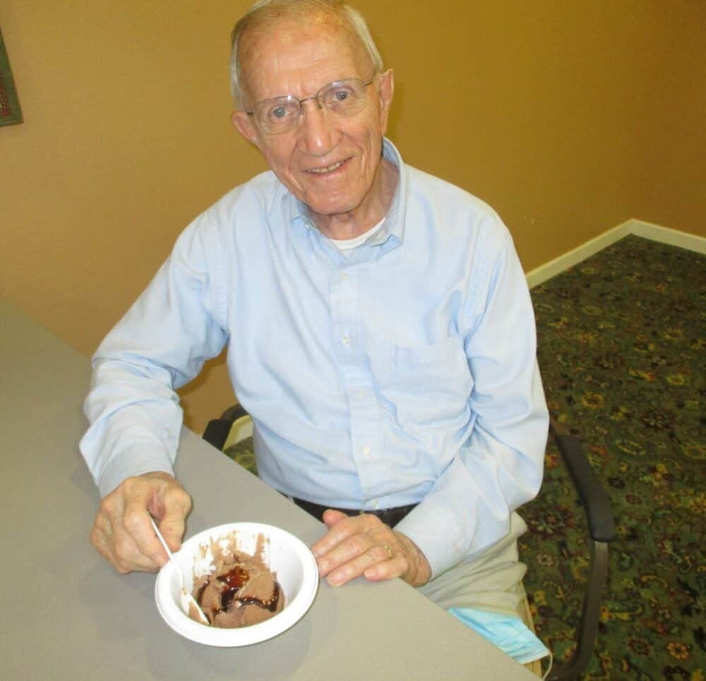 Senior man smiles with a bowl of ice cream at a senior community in Perrysburg, Ohio.