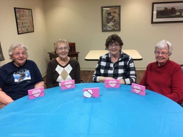 Four senior women smile with their finished crafts a senior community in Perrysburg, Ohio.