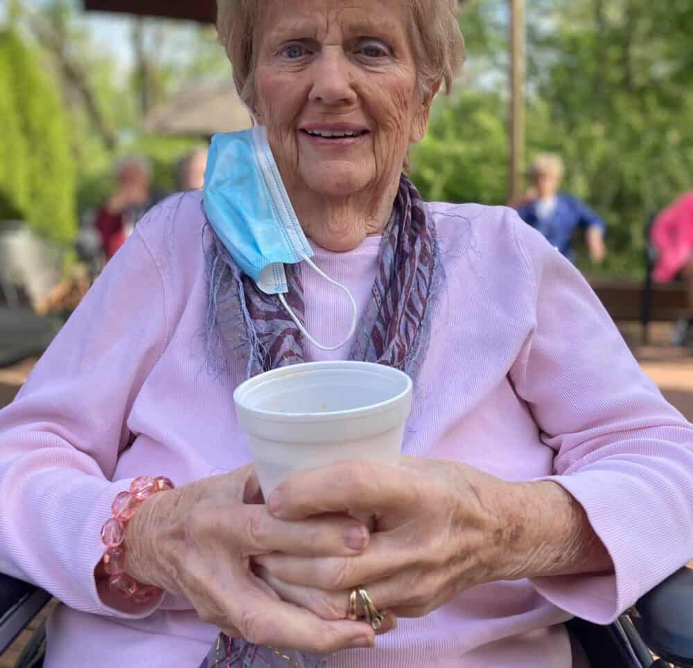 Senior woman enjoying a drink outside at Country Charm senior living in Greenwood, Indiana