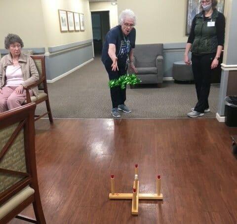 senior woman plays ring toss at Vintage Gardens, a senior living community in St. Joseph, Missouri.
