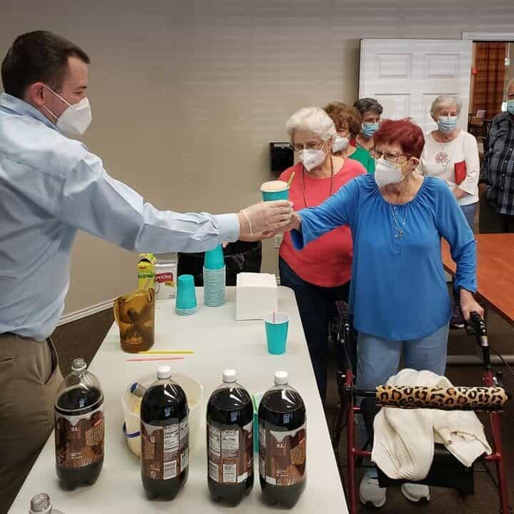 Employee serves root beer floats to seniors at a senior living community in San Antonio, Texas.