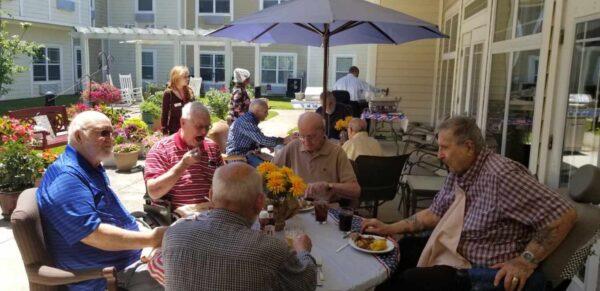 Group of senior men eat together outside at a senior living community in Dayton, Ohio.